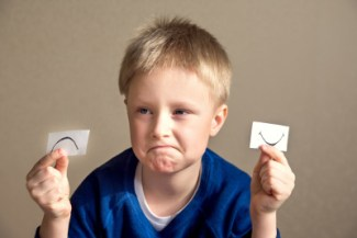 Young boy select between positive and negative expressions