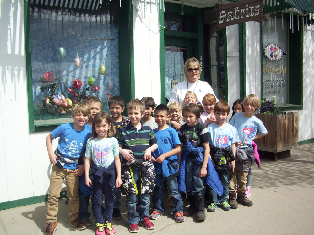 Mrs. Green poses with her class outside the store.
