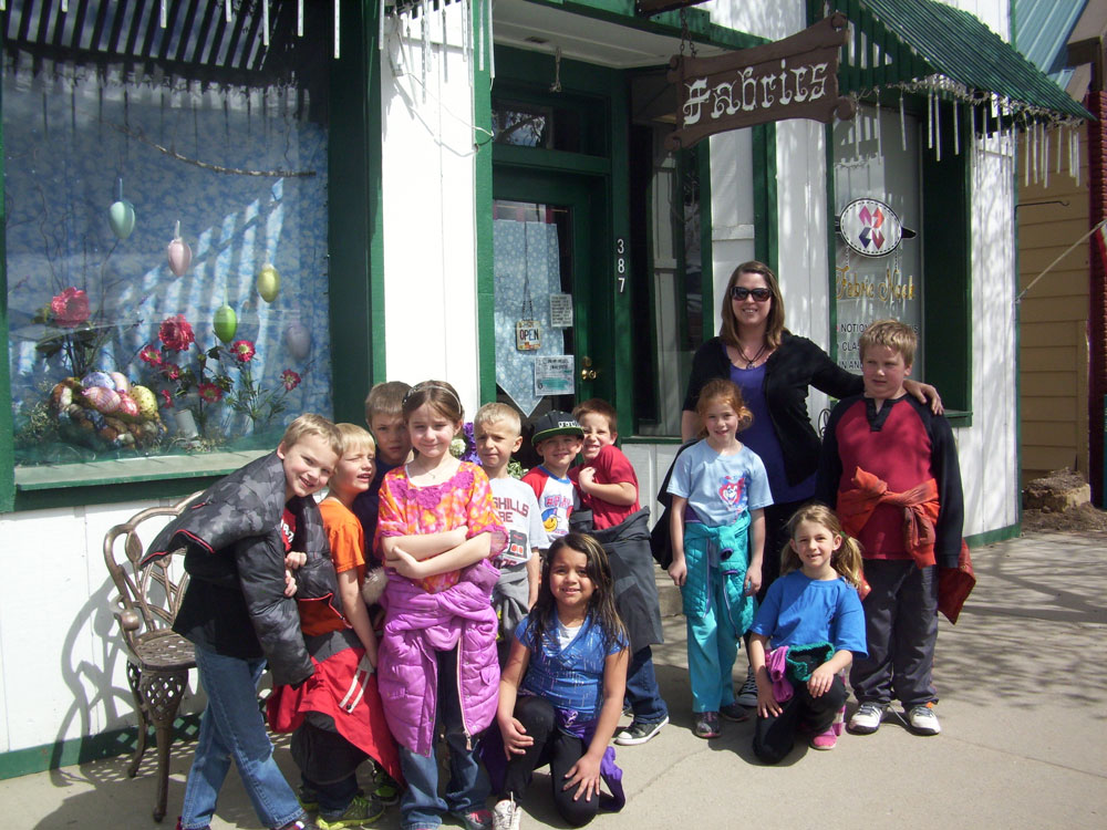 Mrs. Linke poses with her class outside the store.