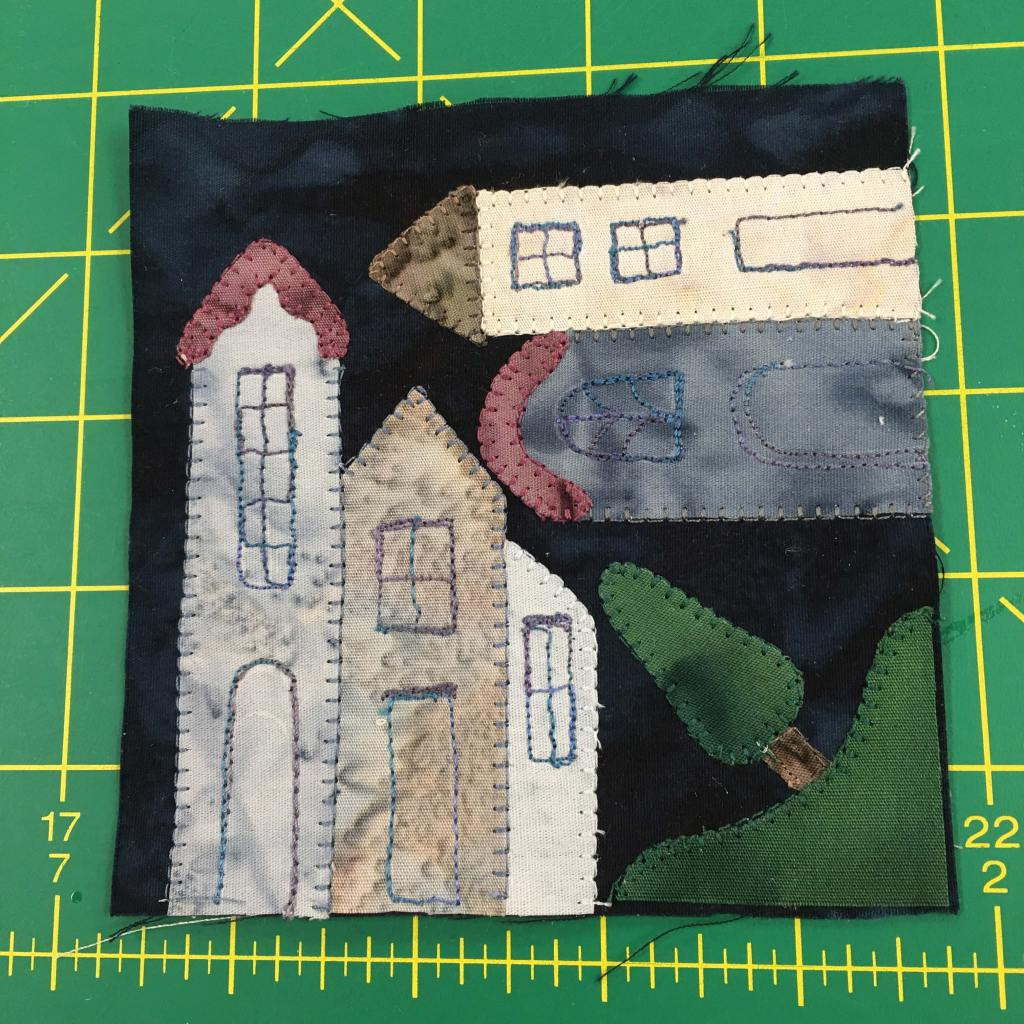 A quilt block on a green background depicting townhouses and a tree. The tree is in the corner, while the townhouses are both vertical and horizontal as if built on a corner.