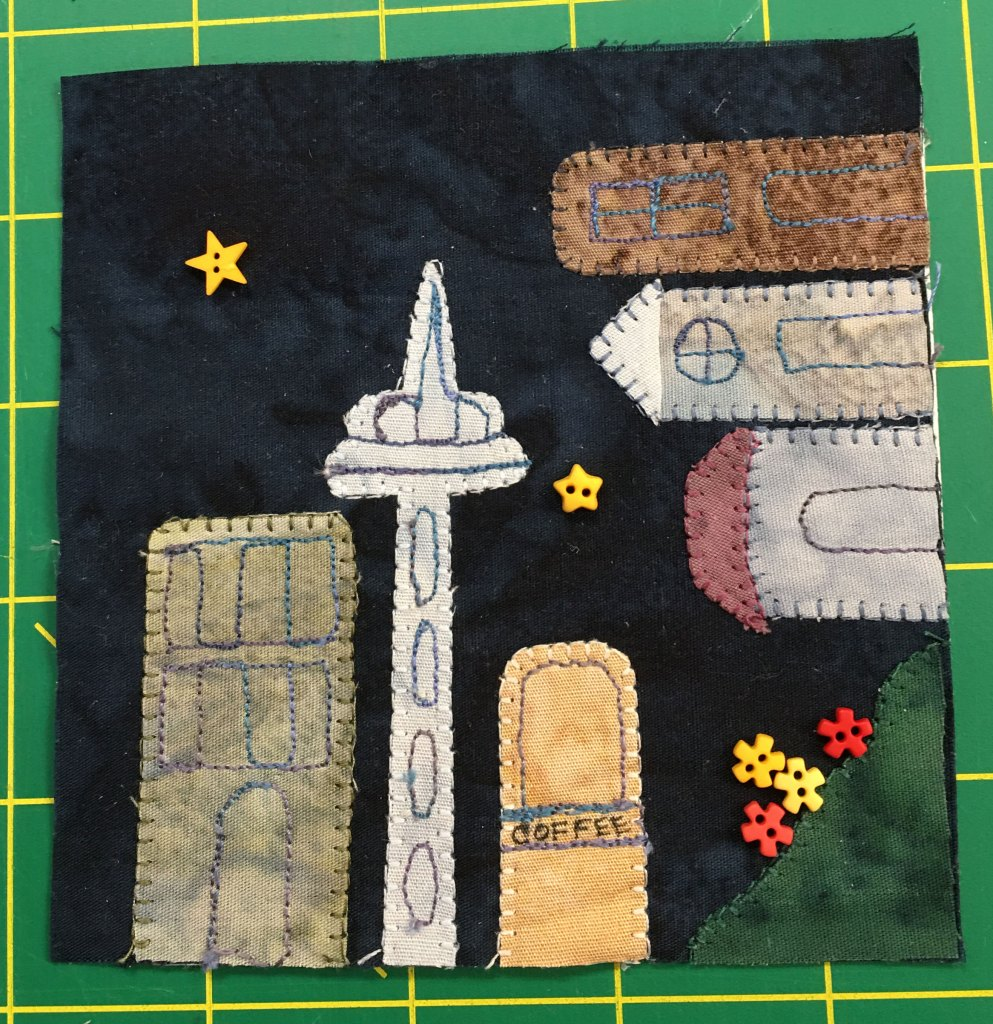 This quilt block features building going around a corner with buttons depicting flowers in the bottom right. The space needle, a tall building with a particular shape, sits next to a coffee shop.