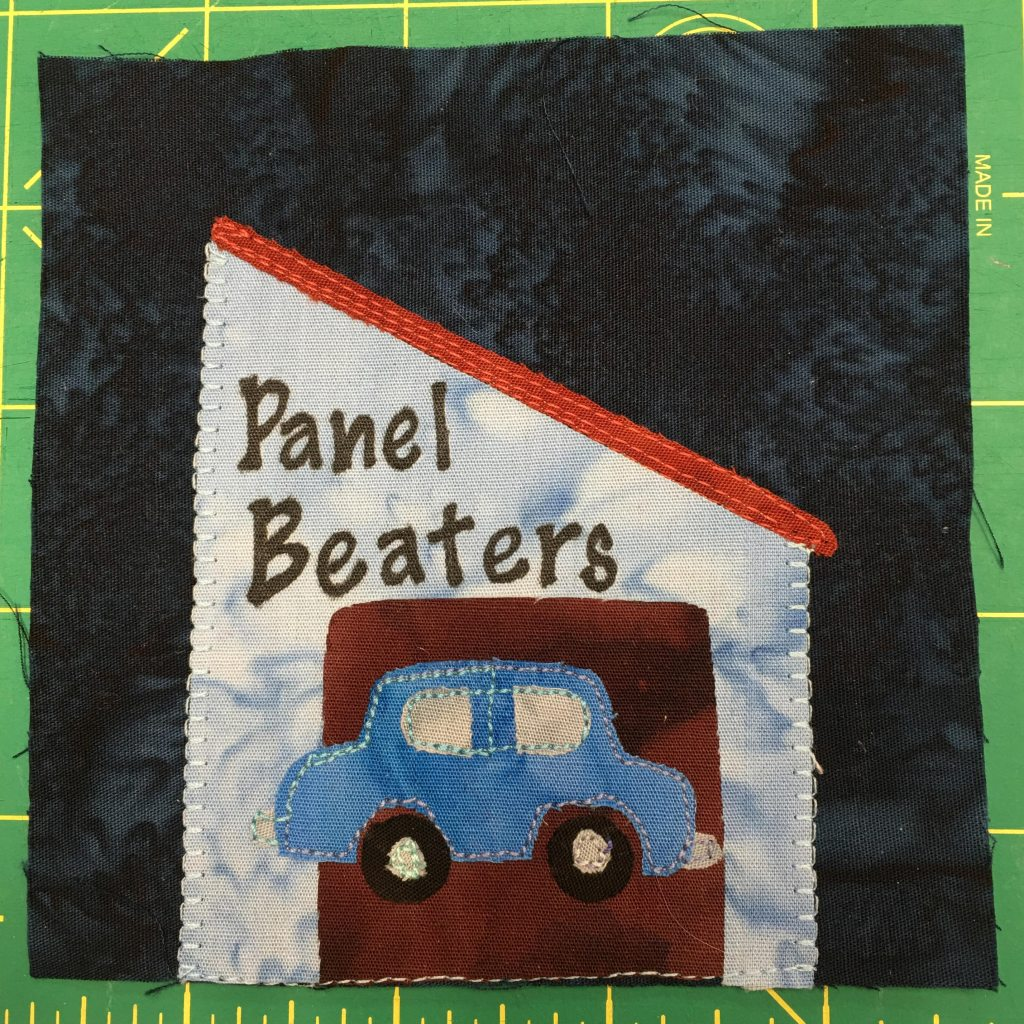 This quilt block shows a panel beater autobody garage. There is a blue car on the front of a building with a red angled roof.