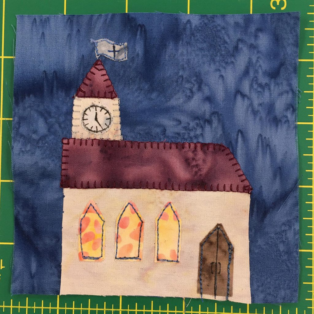 This quilt block shows a church with a steeple on the left. On the steeple is a clock. The church windows are a splotchy yellow-orange fabric indicating stained glass windows.
