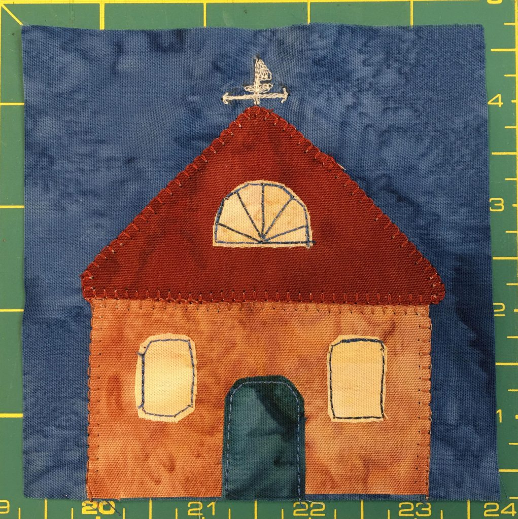 This quilt block shows an orange house with a door in the center. The orof is a perfect triangle and is red. There is a half-circle window in the roof, and on top of the roof is a sailboat weathervane.