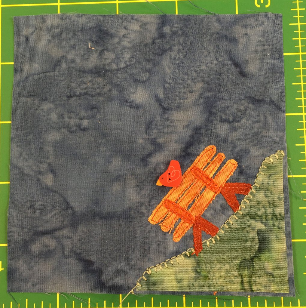 This quilt block shows a blue gray background and a patch of grass in the bottom right. On the patch of grass is an orange bench and on the the bench is a little red bird with a yellow beak facing left.