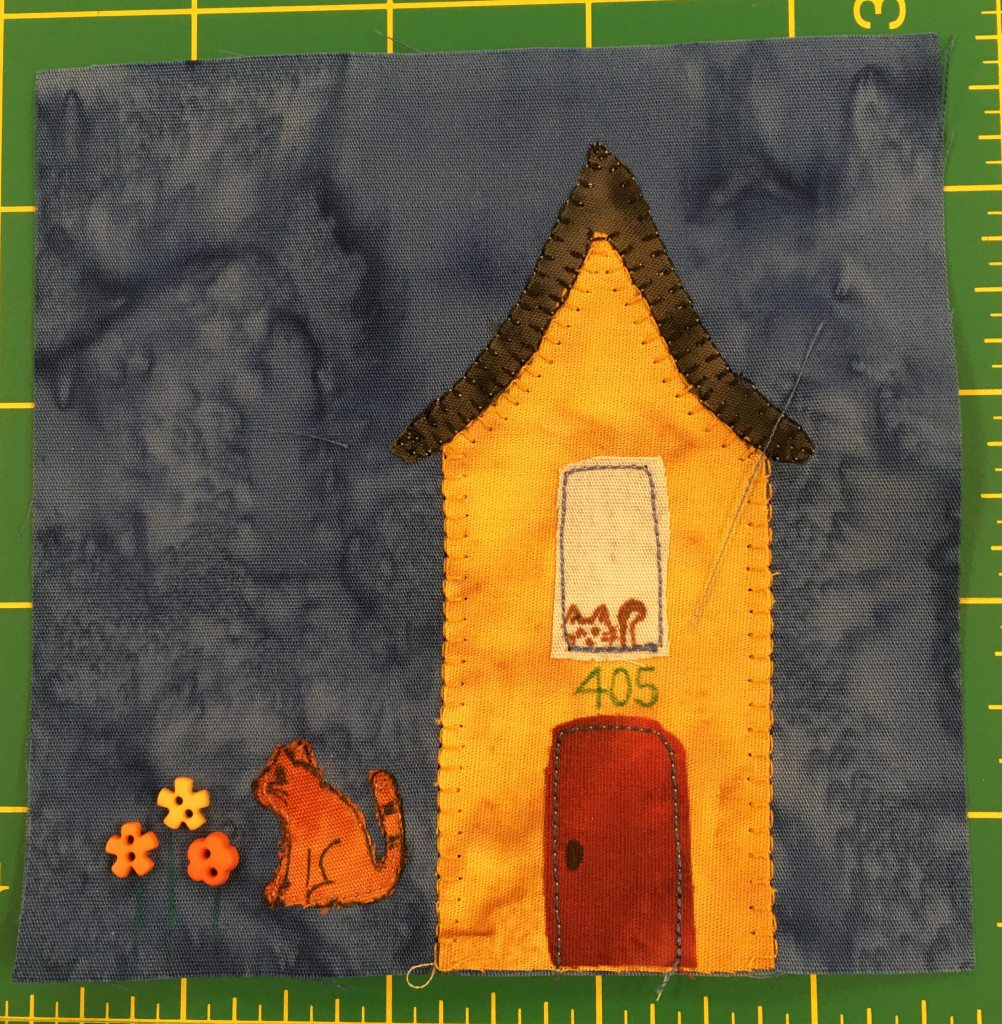 This block shows a tall yellow-orange house with a red door. In the tall window above the door you can see a cat peering out. To the left of the building you can see a cat sitting next to some flowers which are signified by some colorful fun shaped buttons.