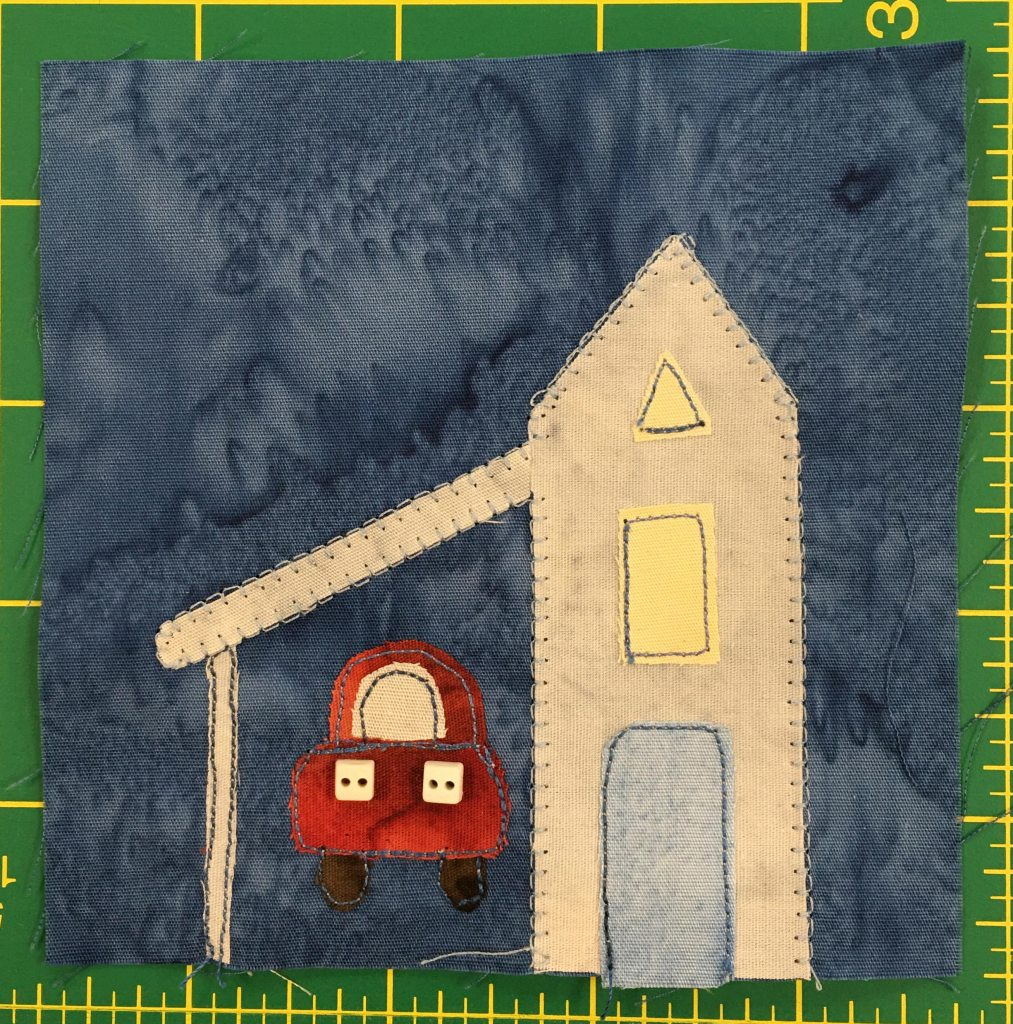 This quilt block shows a tall skinny building with a triangular roof. It has two windows, the top being a triangle as well. Attached to the left of it is a covered car port where a red car is parked.
