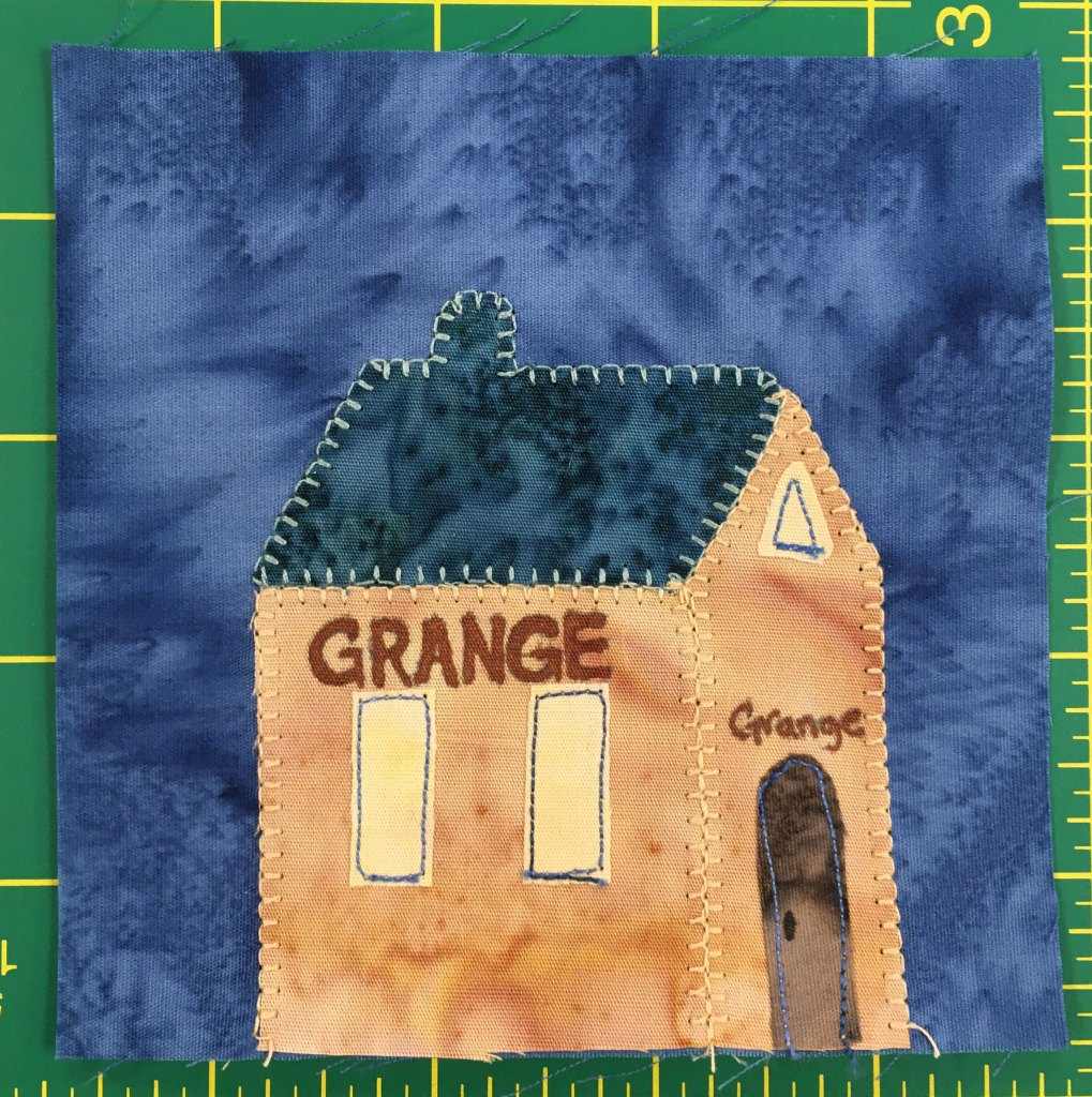 """This quilt block shows an orange building from a side angle with a dark blue roof. There are two tall windows on the side and a brown door on front. Across the side and the front is the word, """"Grange."""""""
