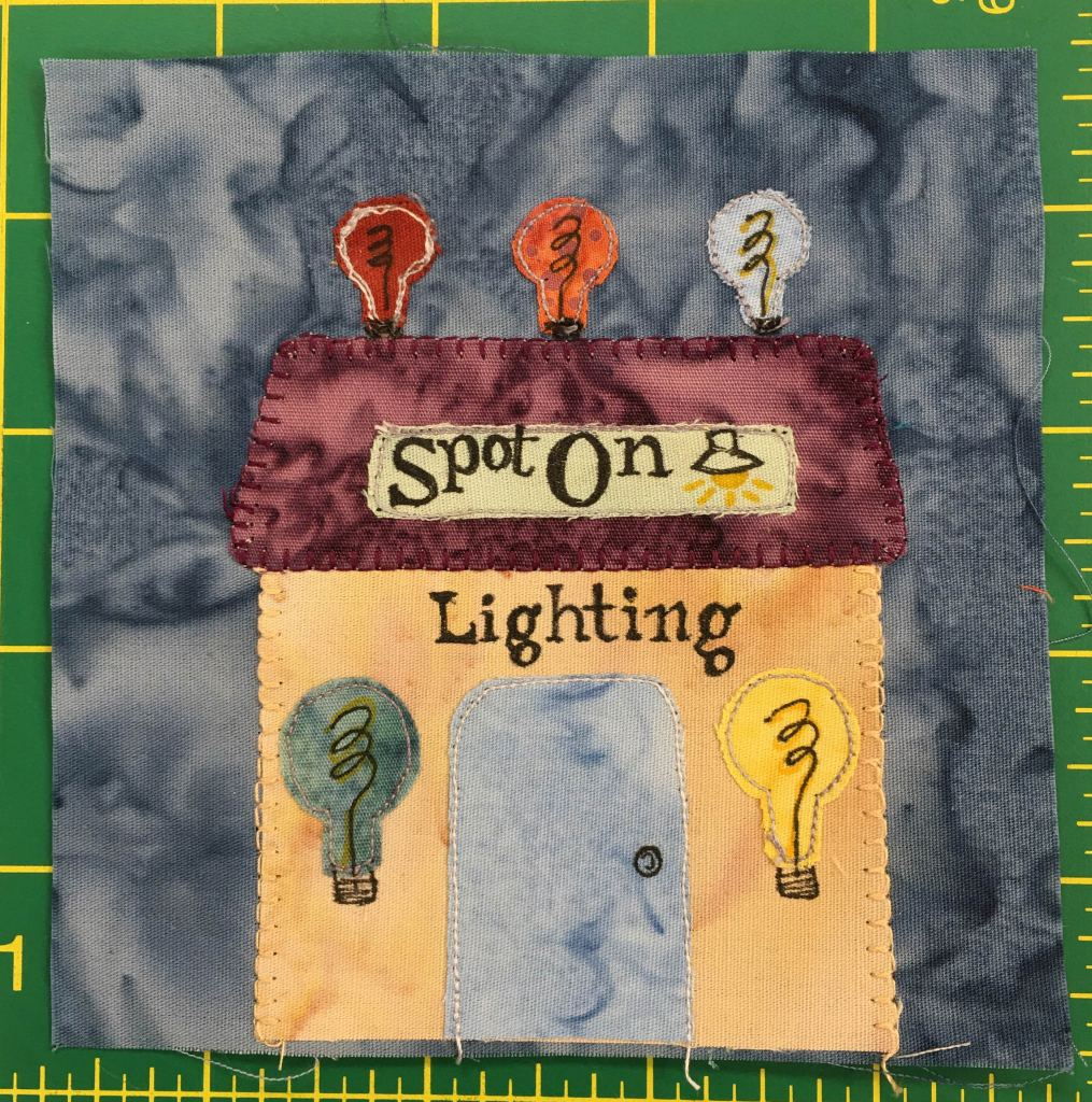 """This quilt block shows a yellow building with three lightbulbs on top. There are also two large lightbulbs to either side of the big gray door. There is a sign on the square flat purple roof that reads, """"Spot On."""" Underneath that on the building is the word, """"Lighting""""."""" The lightbulbs are different colors ranging from red to orange to blue."""
