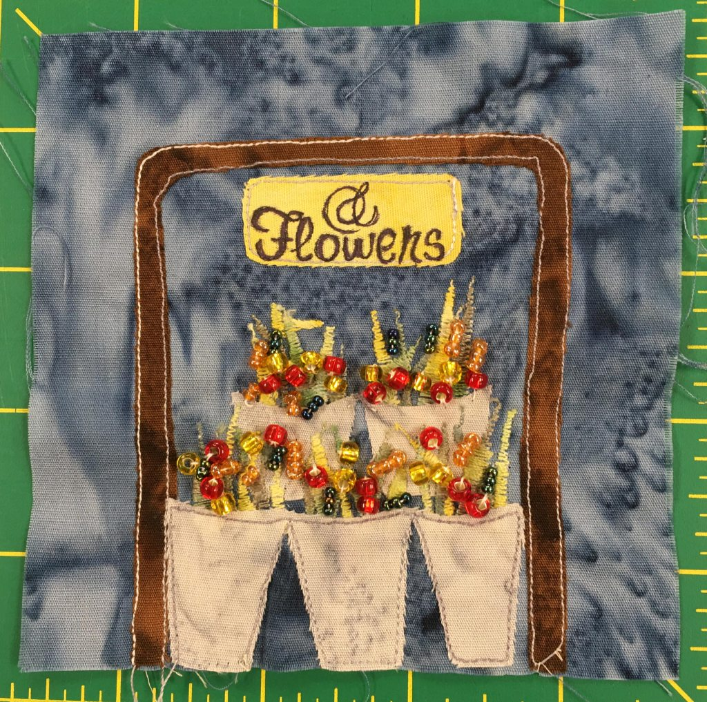 """This quilt block shows a flower stand: lots of baskets of flowers encased in a brown square bracket with a sign on top that reads, """"Flowers."""" The flowers in the vases are created with shiny little bead like buttons."""
