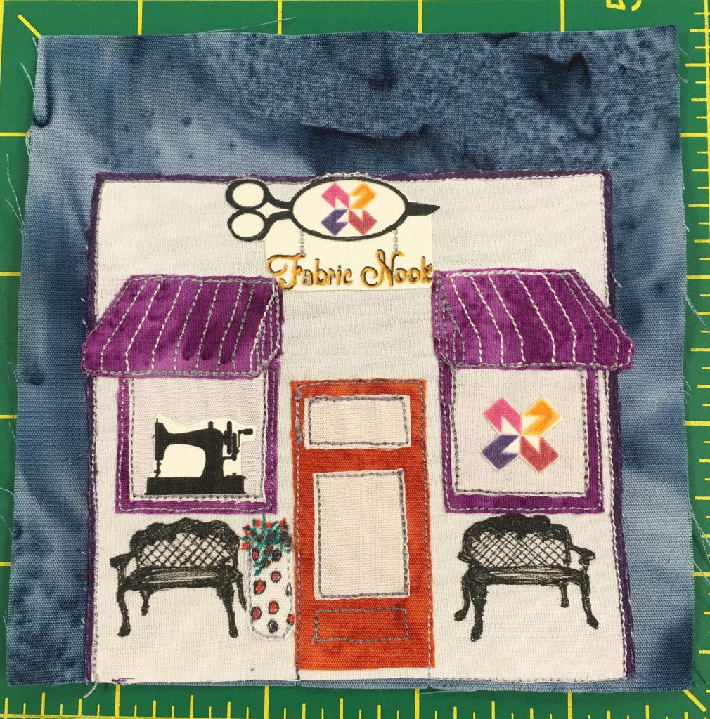 This quilt block shows the front of the Fabric Nook store, complete with the logo at the top of the building. It is a square all white building with no separate roof. There are two windows on either side of the center door with purple canopies. On the left is a silhouette of an old school sewing machine, and on the right is the Fabric Nook quilt block logo. There are two ornate benches in front of the store, as well as a planter that is decorated with polka dots. The door is orange with two sections for glass.