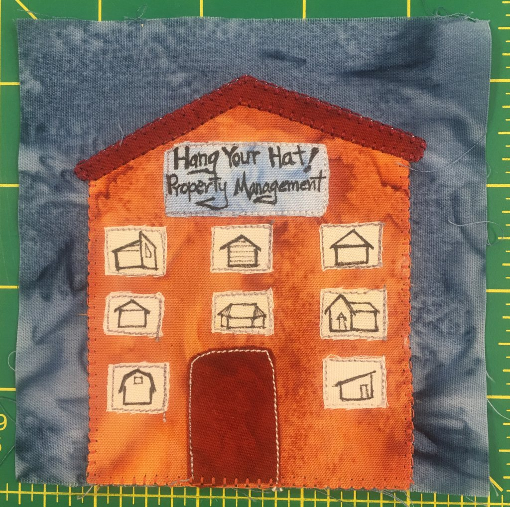 """This quilt block shows a large bright orange building with many windows. The roof is triangular and red, like the door. There are eight windows, and in each window are images of different kinds of dwellings. The sign at the top of the building has written on it, """"Hang Your Hat Property Management."""""""