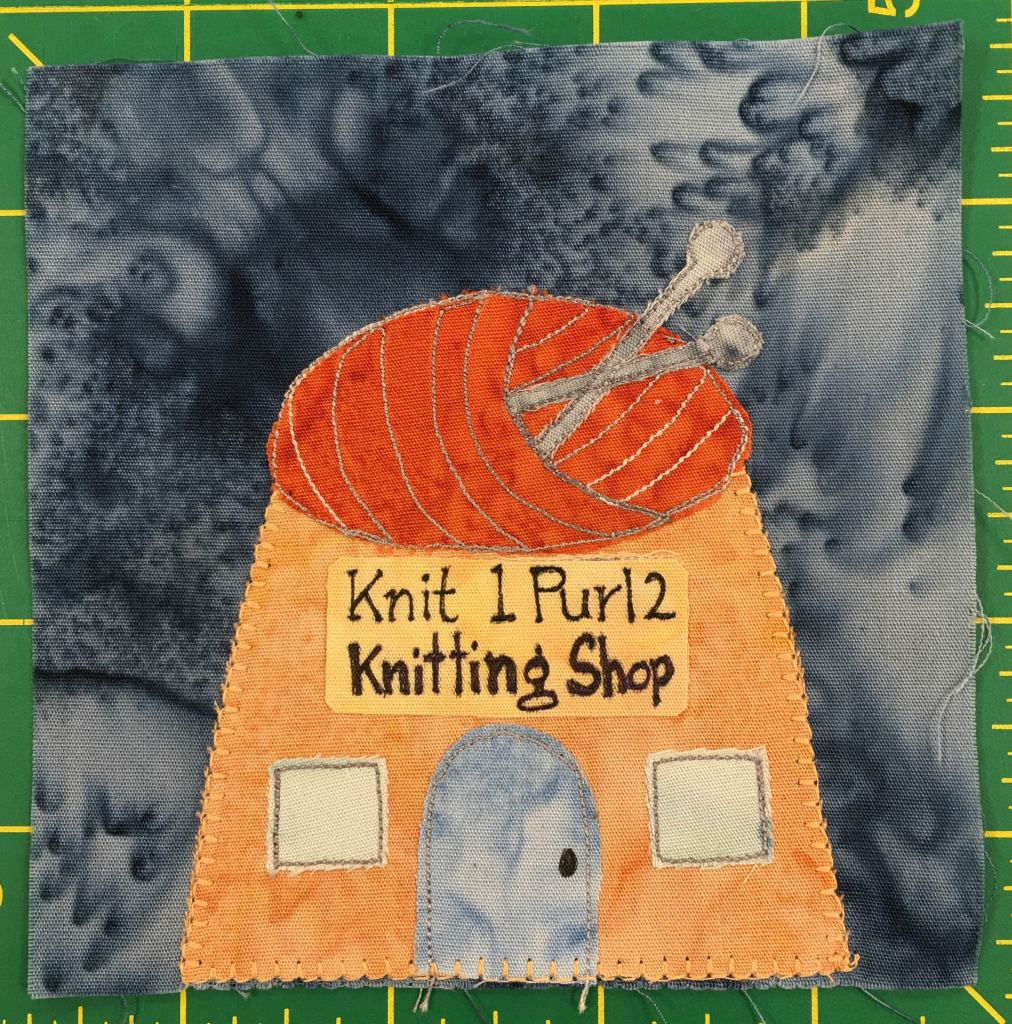 """This quilt block shows a somewhat squat building whose roof looks like a ball of orange yarn with knitting needles poked into it. Below the orange yarn is a light orange exterior with a big yellow sign on the front hat says, """"Knit 1 Purl 2 Knitting Shop."""" There are two blue tinted windows on either side and a gray door below it."""