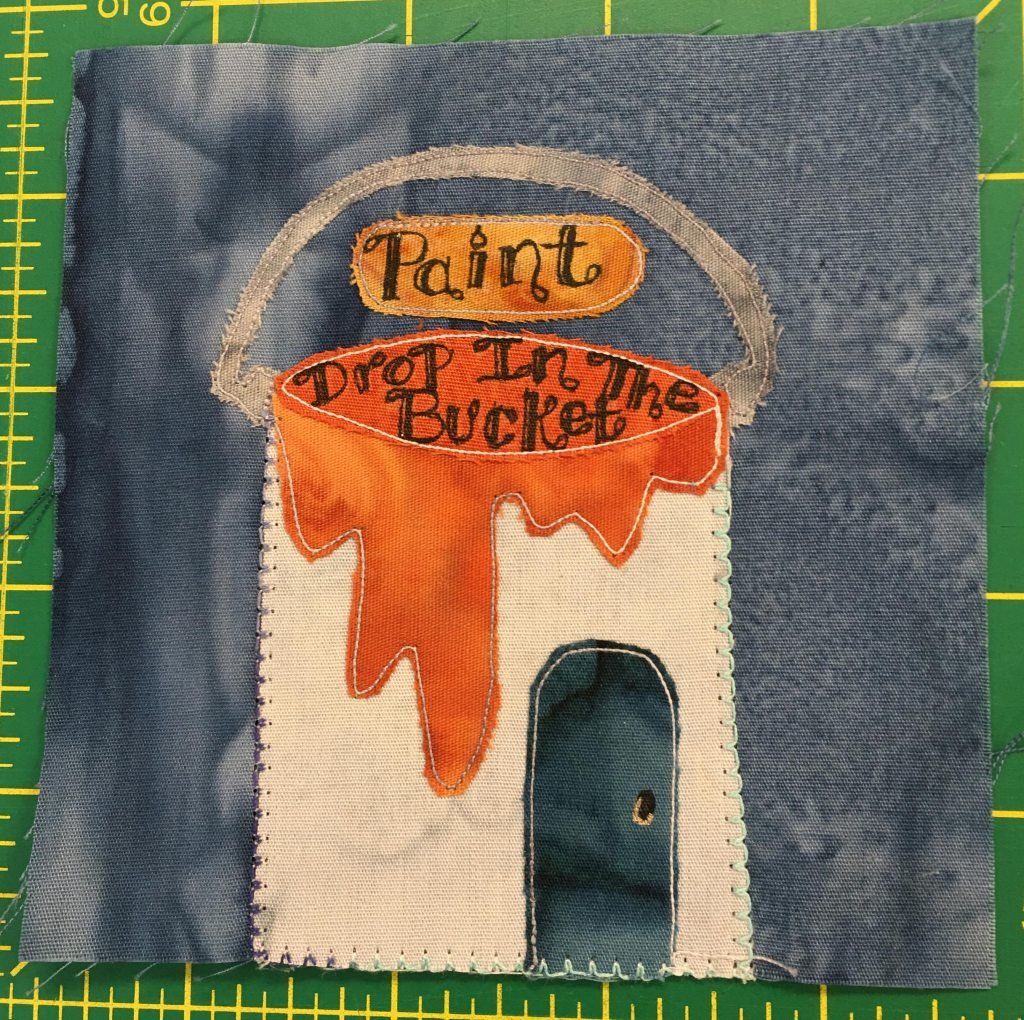 """This quilt block shows a building shaped like a paint bucket. The paint that is glazing over the side of the can is orange. The building or can is white, and there's a semi-circle handle over the roof. The sign above the open hole in the bucket reads, """"Paint."""" But in what would be the bucket are letters written in on the orange background that say, """"Drop In The Bucket."""""""