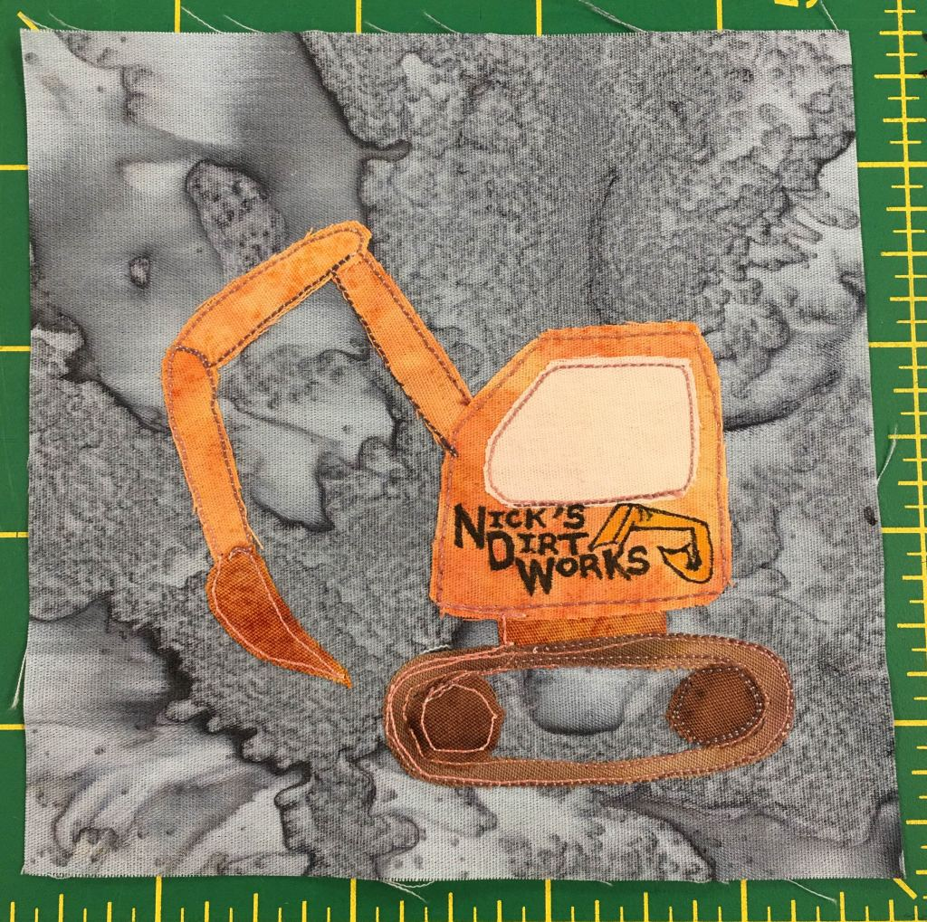 """This quilt block depicts an pretty detailed orange excavator. On the side of the excavator door are the words, """"Nick's Dirt Works"""" along with an outline of another excavator."""