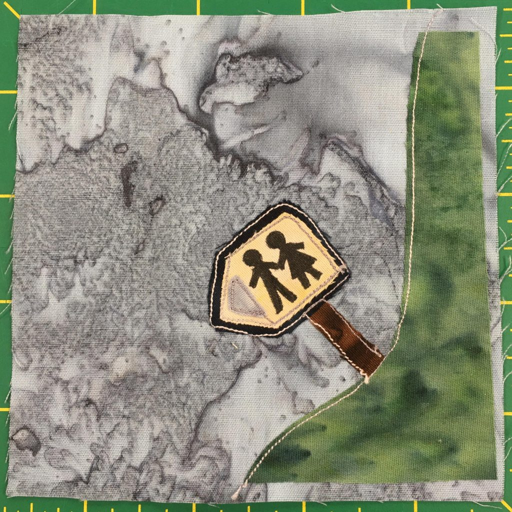 """This quilt block is a corner block. A smooth patch of grass extends from the bottom right upwards tot he upper right indicating a """"turn"""" in the quilt's path. On the patch of grass is a sign with figures on it denoting a man and a woman in a dress that indicate the direction of the restrooms presumably. The sign is on a brown stick and is yellow itself with a white triangle indicating the direction."""