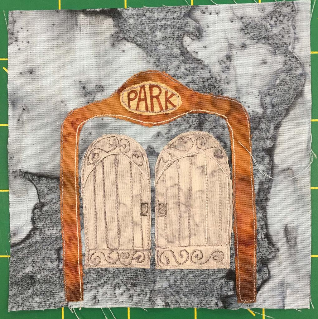 """This quilt block shows a large gate against a gray background. The gate is huge, with a brown presumably metal frame forming an arc over the swinging double doors. Overhead, as you would walk under, is a sign in yellow that has the word, """"Park"""" on it. The doors themselves are embellished with design, and looks somewhat like fancy saloon doors, or the even the pearly gates of heaven."""