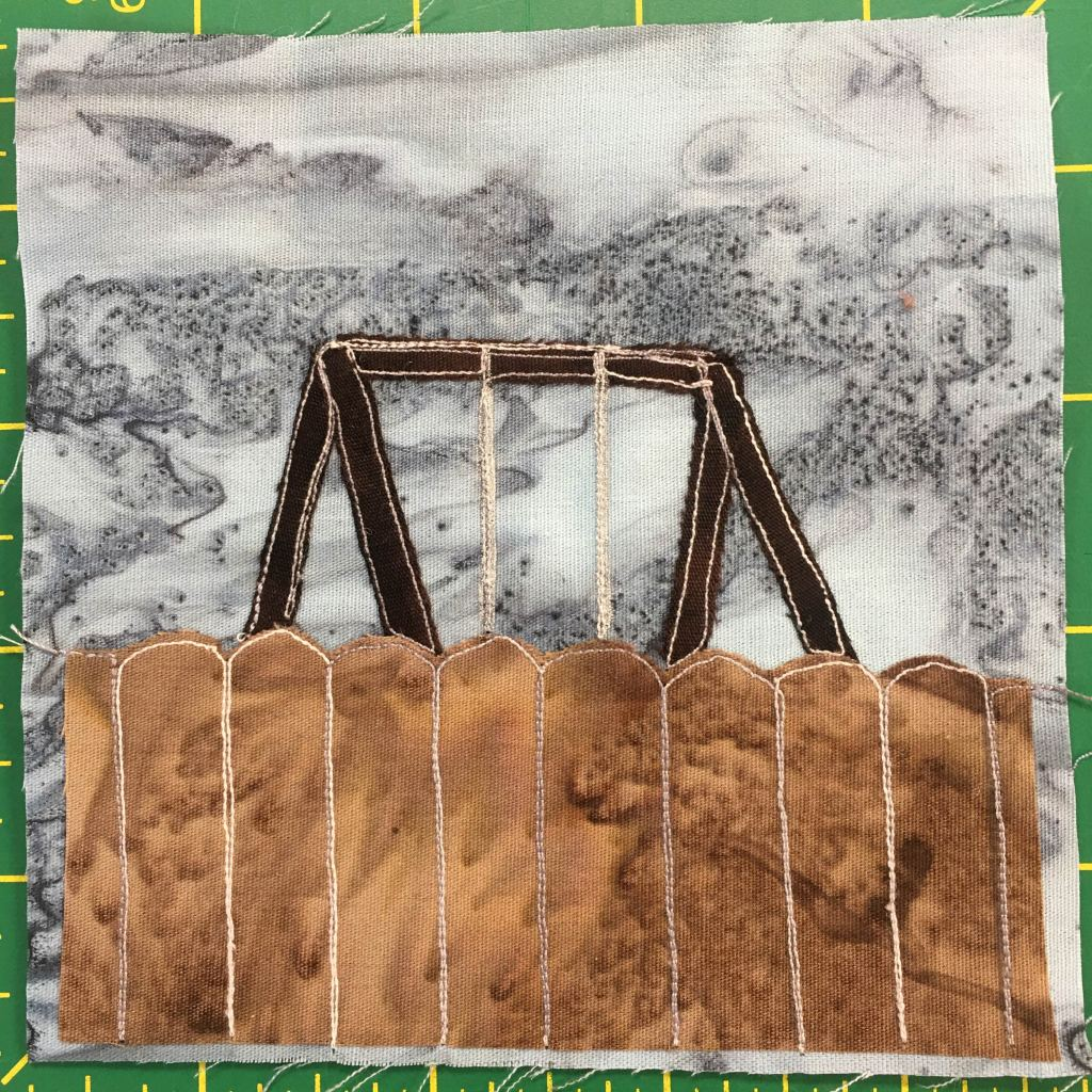 This quilt block shows a brown fence, like in the previous blocks, coming up just short of halfway. Above the fence you can see the top bars and chains of a swing-set. Both of these are against a gray splotchy background.