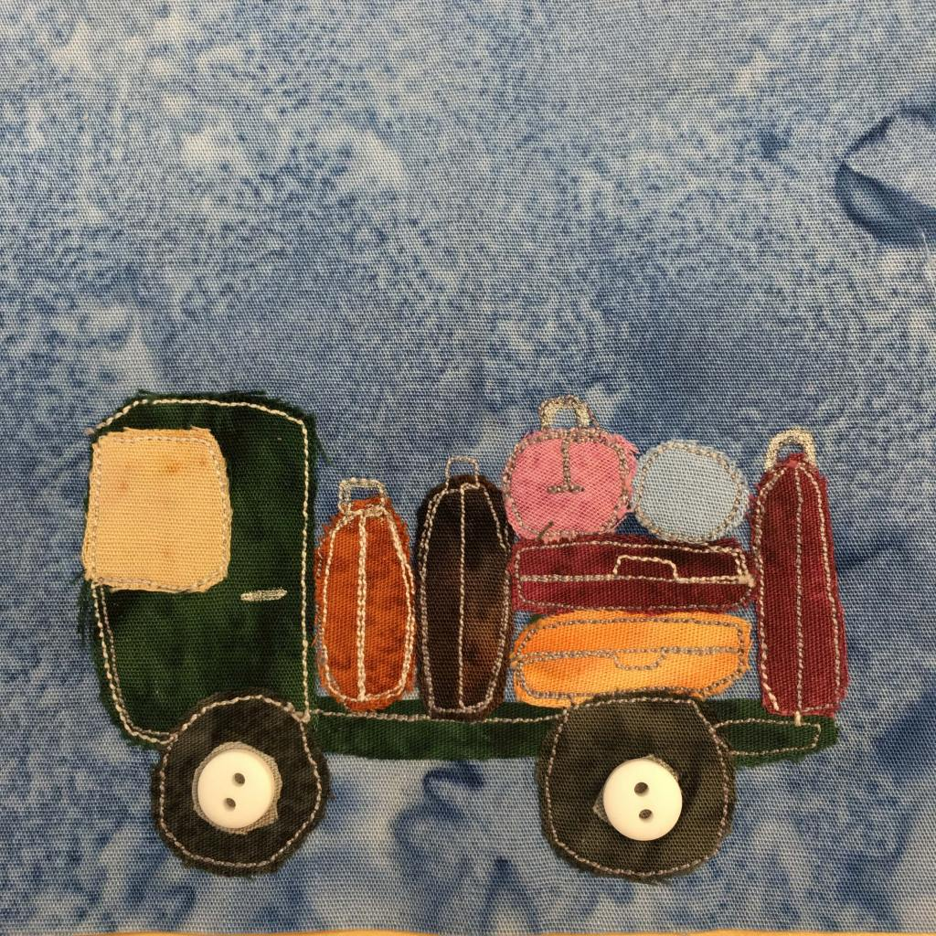 This quilt block shows a green luggage truck from the side against a blue salmon-patterned background. The truck itself is just a flatbed, and is made up of a dark green fabric. The cab has a yellow fabric windshield, and on the flatbed behind it are various suitcases. Each suitcase is a different shade of orange and brown, with one pink and one blue suitcase. There are two dark wheels below with fairly large white two-holed buttons on them indicating the axles or hubcaps.
