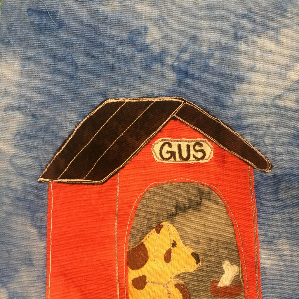This quilt block shows a dog house against a blue salmon-patterned background. The dog house has a very dark brown roof and is made of bright orange fabric. The inside is a gray fabric, but also inside is a spotted yellow dog. The dog is yellow with brown spots on it. There is also a dog bowl with a white bone in it. The bowl and bone are drawn with a pen.