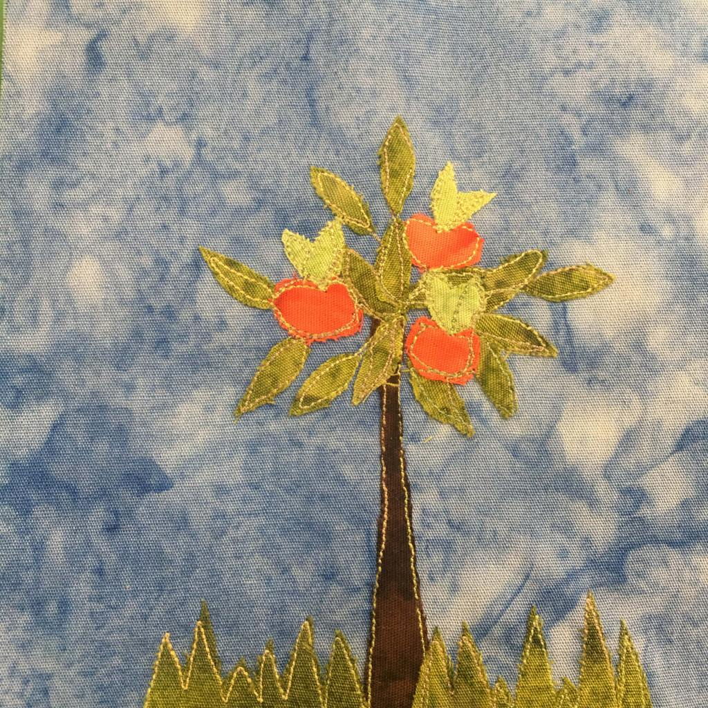 This quilt block shows an apple tree. Much like the previous orange tree there are jagged shaped patches of grass at the bottom of the block. Then there is a trunk that is dark brown and lined by yellow stitching. At the top are many scattered leaves and large round reddish-orange apples. Each apple has a light green stems and leaves sticking out of the top. This is all against a blue salmon-patterned background.