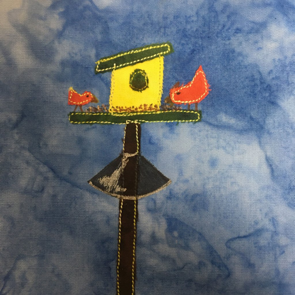 This quilt block shows a bird feeder with two birds on it against a blue salmon-patterned background. The bird feeder is on a black pole with yellow stitching outlining it. On the pole is a cone shape with the broad base at the bottom to keep out squirrels. The cone shape is drawn with pen and has a sheen on it. The bird feeder is yellow with a slanted green roof. The birds sitting on the perch are a red-orange with a yellow stitching outline and drawn beaks.