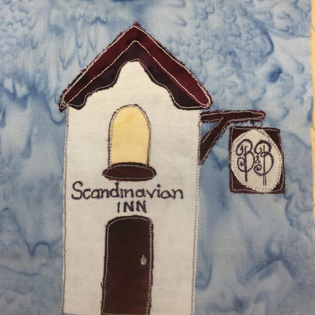 """This quilt block shows a skinny tall white building with dark brown trimming. The roof is triangular with trimming underneath it. There is a yellow rounded window above the door with a window sill that is dark brown. Below that are the words, """"Scandinavian Inn"""" and below that, a dark brown door. On the side fo the white building near the roof are two boards jutting out and holding up a sign. The sign has fancy scripted B's on it indicating it is a Bed and Breakfast."""