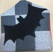 A quilt block looking pattern with a black bat on it in silhouette. It's against a light gray checkered background. The fabric is in the shape of the end of a flyswatter.
