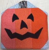 A quilt block looking pattern with an orange grinning jack-o'-lantern. It's against a light gray checkered background. The fabric is in the shape of the end of a flyswatter.