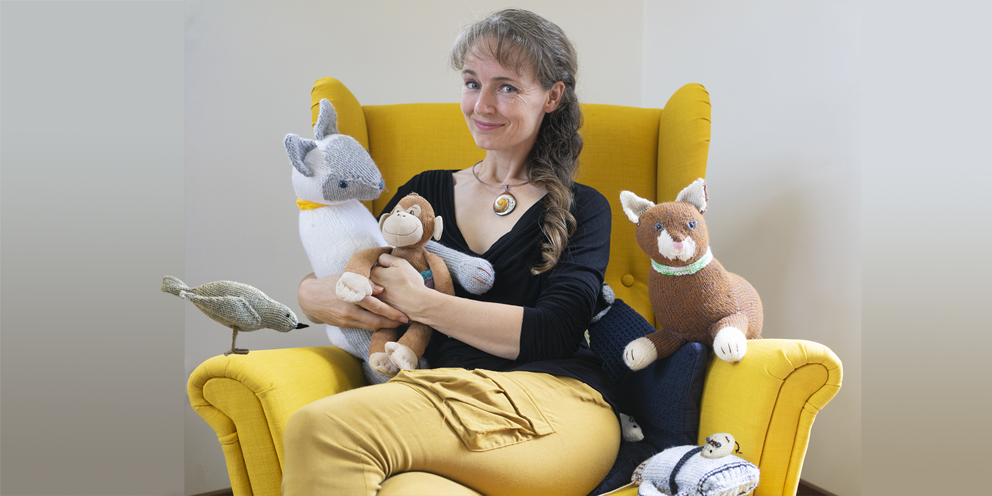 Author and illustrator Tina Wilson sitting with her characters from Monkey's Great Adventures