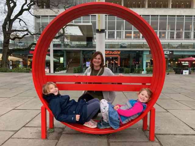 Kids and mum sat on bench sculpture outside Southbank Centre in London