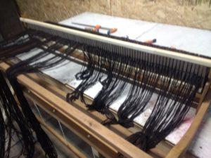 On égalise les fils de chaîne avant de les sèparer entre fentes et trous et de les nouer