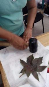 On martèle la feuille avec un marteau de carreleur en caoutchouc, ici feuille de ricin