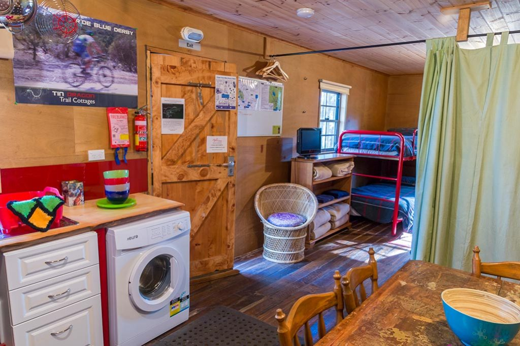 View from kitchen dining area to bunk beds inside the Settlers Hut : Blue Derby budget accommodation