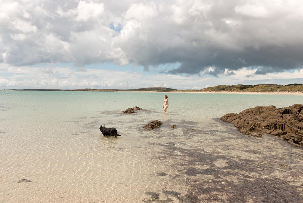 Top skinning locations in Tasmania - In the distance is a woman with no cloths wading through ocean water with her dog