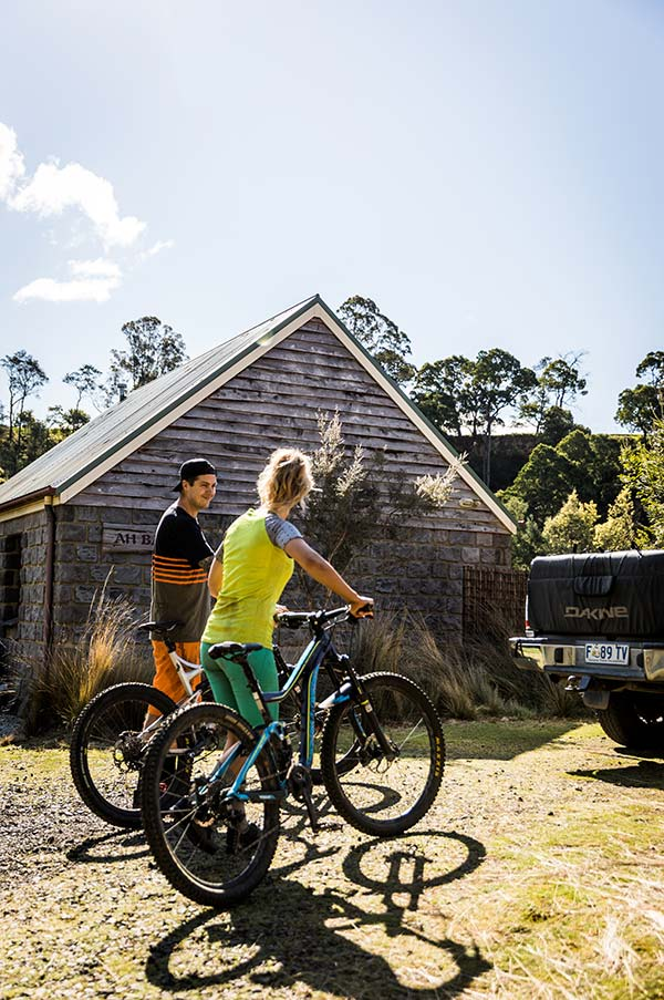 Couple with their mountain bikes outside Ah Back studio cottage near Derby in Tasmania