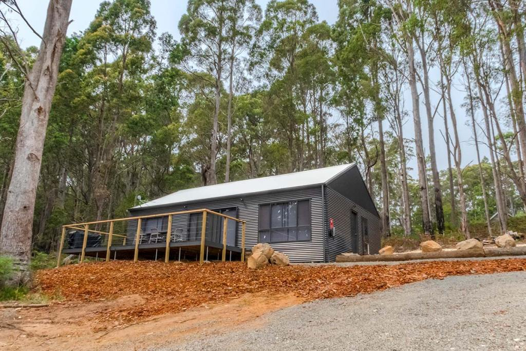 The Barn is a charcoal coloured shed with a front deck sitting on a hill in the bush.