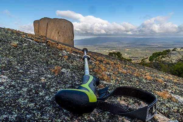 On a large slab of granite is a prone walking stick and in the background is the cube rock.
