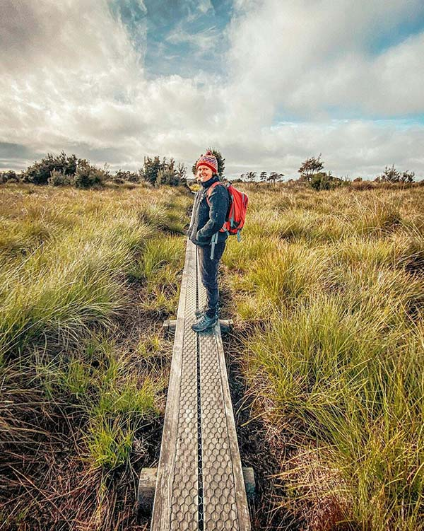 A woman wearing a black coat and a red beanie is standing on a board walk on the button plains, Mount Victoria Reserve in North East Tasmania.