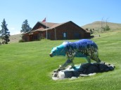 A typical camp cabin in the background with a beautifully carved and painted bear in the foreground. Depicted on the bear are staples of Montana, such as gorgeous mountains and a multitude of wildlife.