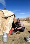 Two Kazakh nomads with their animals offering to share a cup of tea