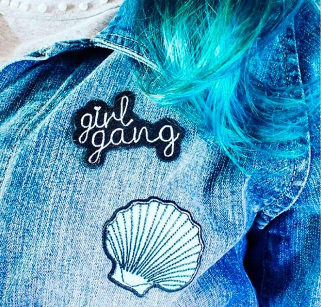 Zoom em uma jaqueta com um patch escrito Girls Gang e outro de concha