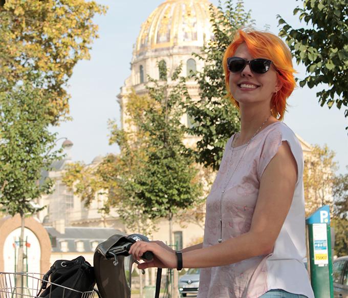 Eu segurando uma bicicleta com Invalides e árvores ao fundo