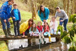 Moms and Children On Bridge At Outdoor Activity Centre