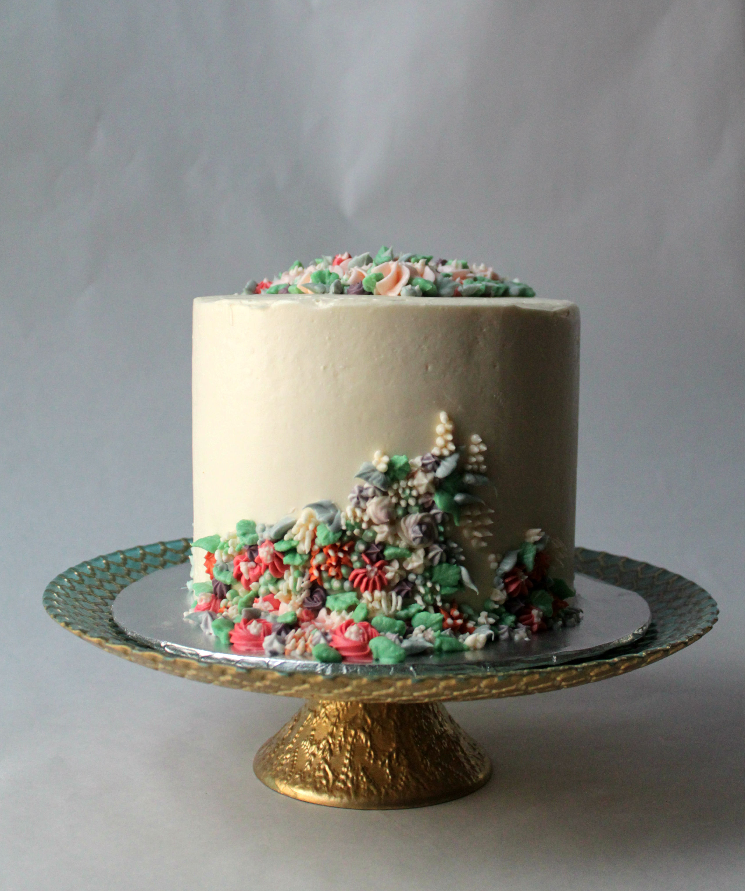 single six inch cake with creeping flowers and other designs in all buttercream