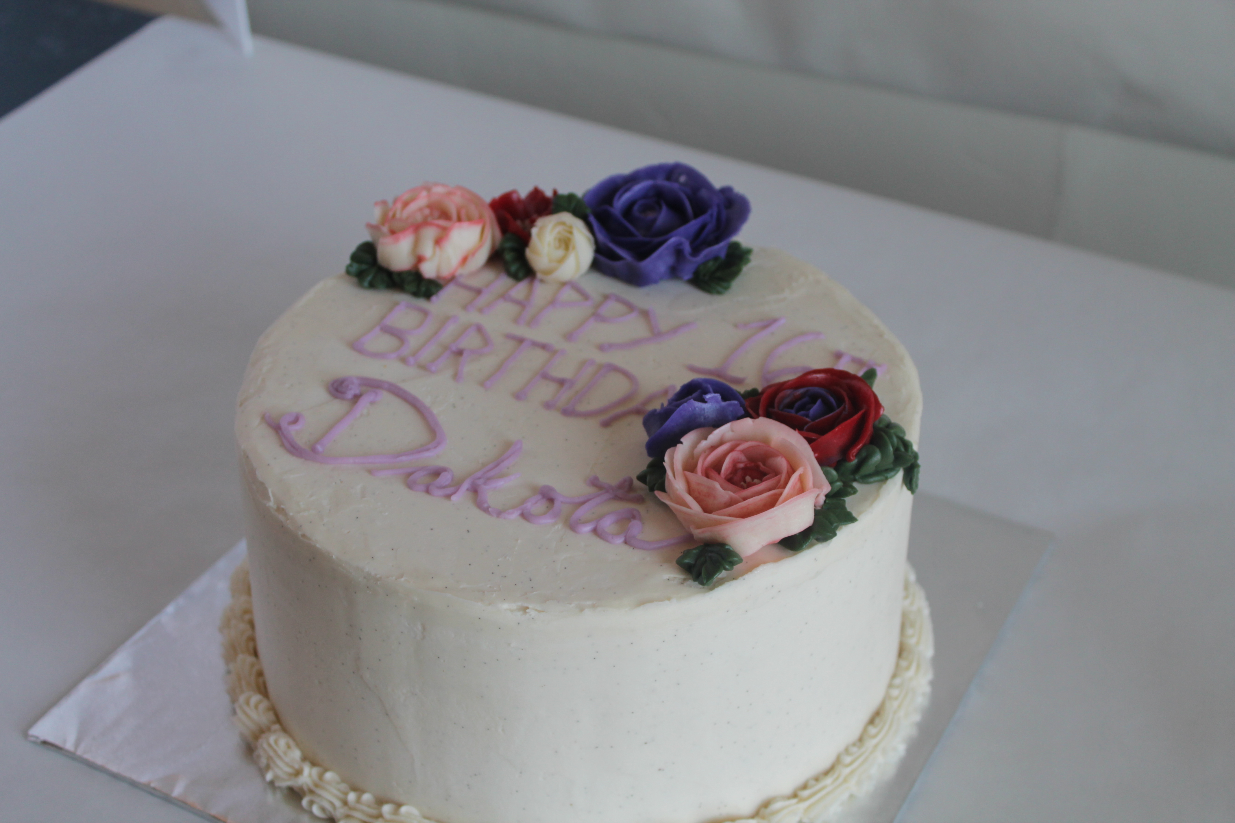 simple birthday cake with buttercream flowers and roses