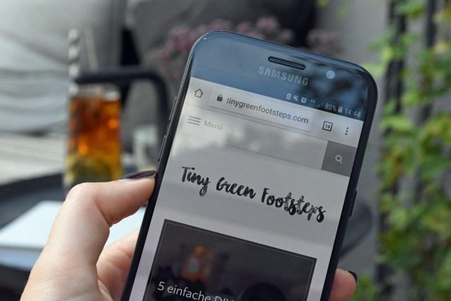 Auf einem Smartphone ist die Homepage von tiny Green Footsteps geöffnet