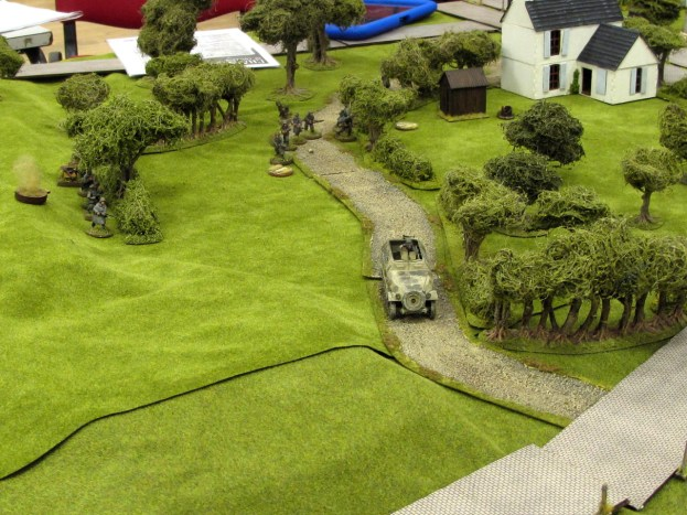 The Hanomag pushes up the road, with the rest of the infantry crossing the start line behind it.