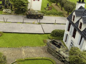 German half tracks barrel up the road, the troop carrier in the foreground using the houses for cover