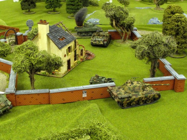 It's all on! A Burning Sherman and an abandoned StuG in the background, with a Panther, carrier and the front of a Sherman in the fore